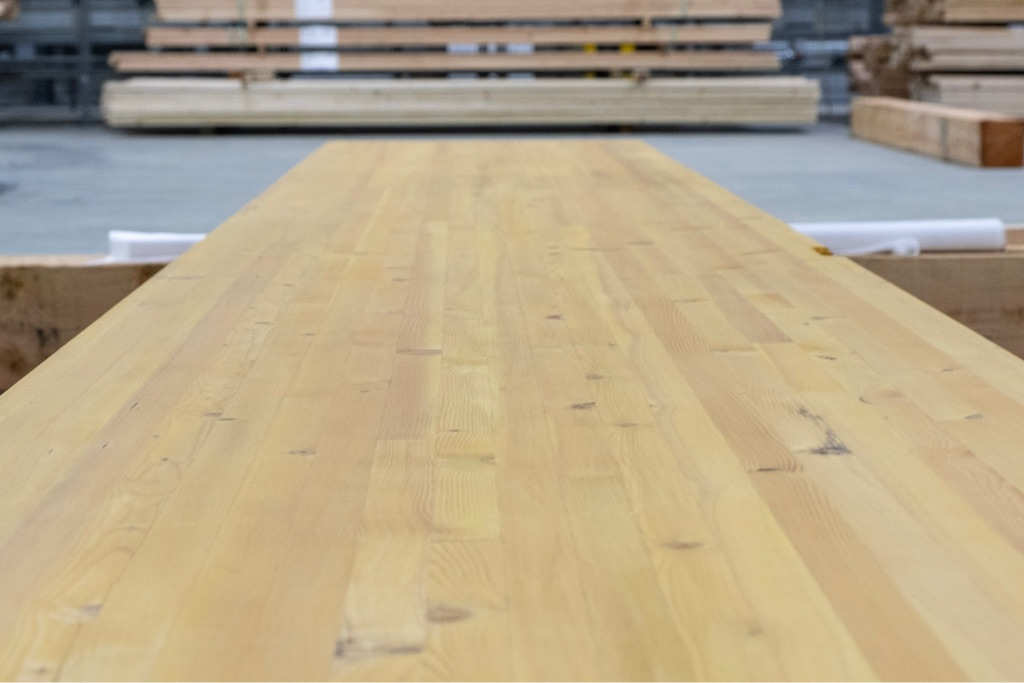 close up of glue laminated timber panel with mass timber facility blurred in the background