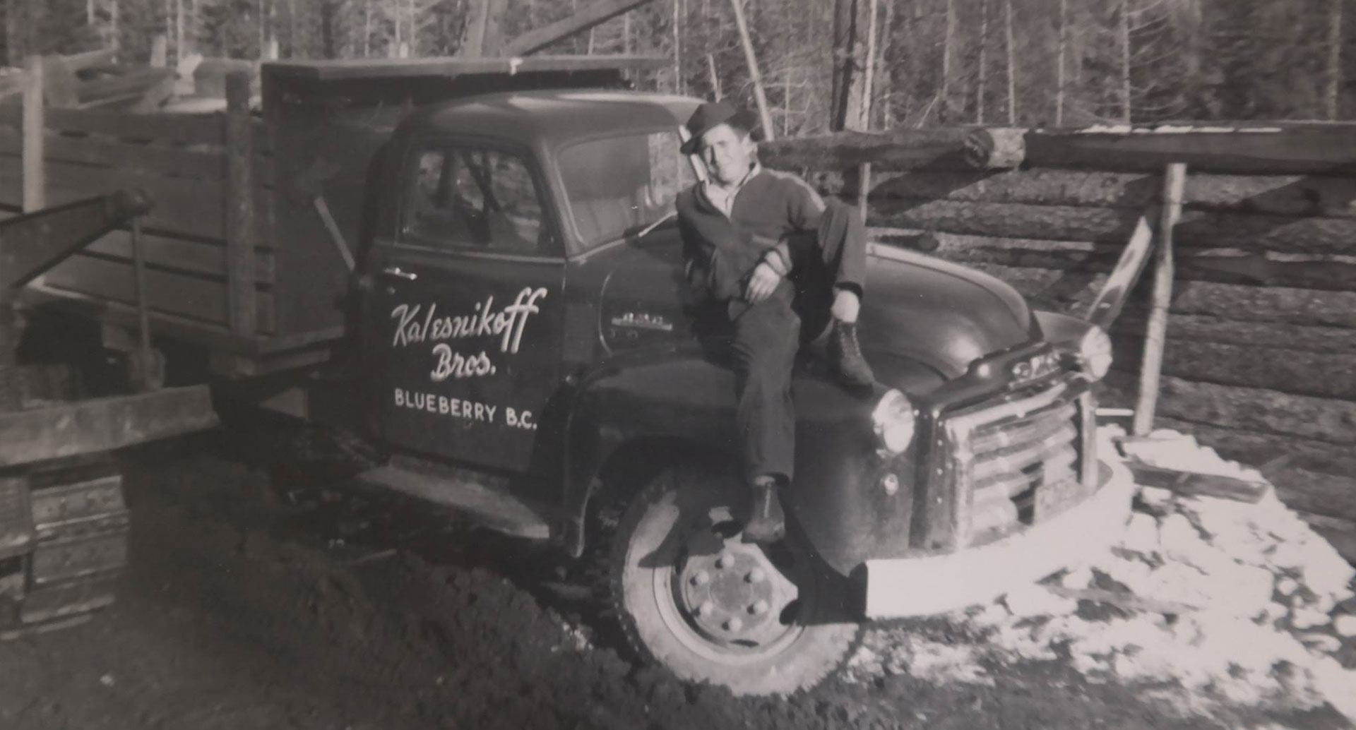 Black and white photo of Kalesnikoff family member sitting on hood of truck