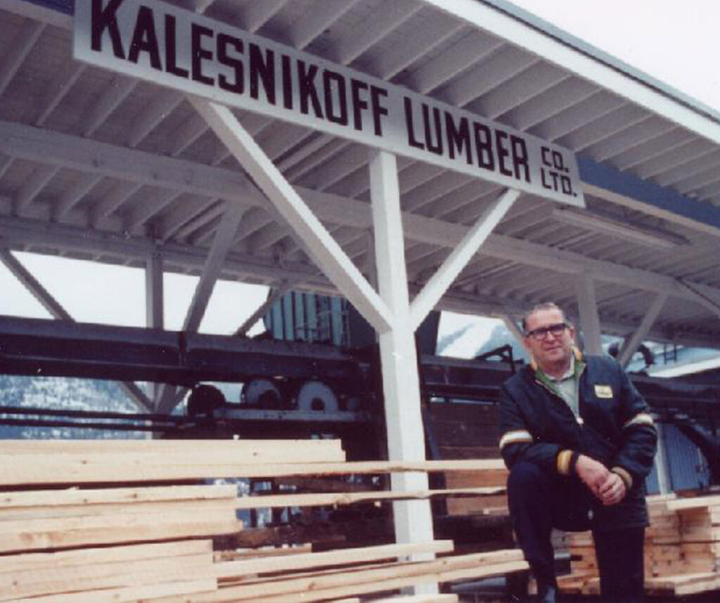 Kalesnikoff leaning on a stack of lumber