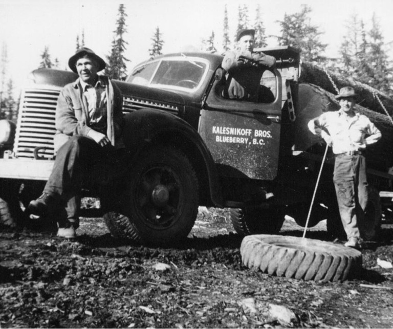 Black and white historical photo of Kalesnikoff brothers by family truck with tire on the ground