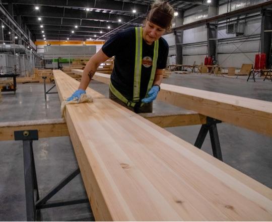 mass timber production line worker laminating engineered glulam beam